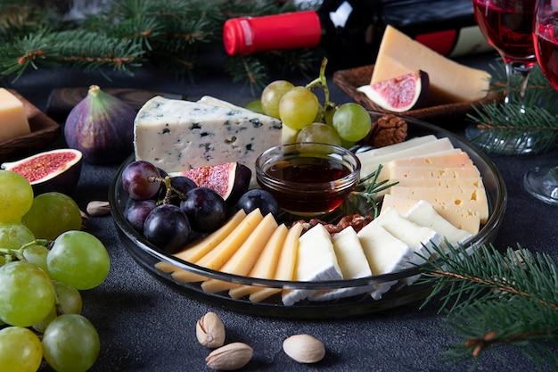 Variedade de queijos e frutas servidas em prato redondo, em fundo cinza escuro com taças de vinho. lanche de festa de ano novo