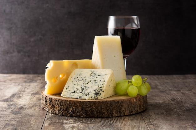 Variedade de queijos e vinho na mesa de madeira.
