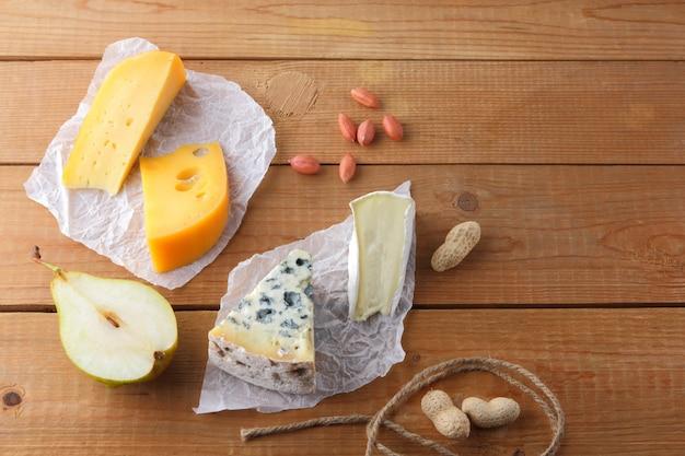 Variedade de queijos, peras e amendoins em papel vegetal. camembert, queijo amarelo duro, dorblu em tábuas de madeira. laticínios, meias peras e nozes