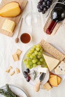 Variedade de queijos servidos com mel, uvas, pão, vinho e alecrim