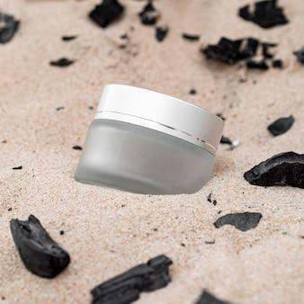 Variedade de recipientes de hidratação para cuidados com a pele na areia