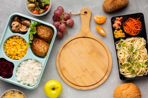 Variedade de refeições para cozinhar em lote com placa de madeira