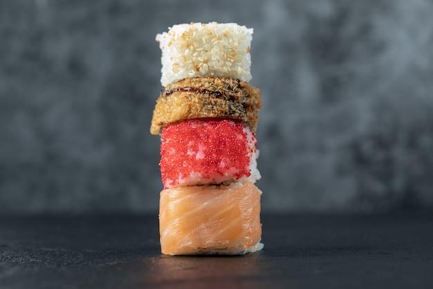 Variedade de rolos de sushi isolados na mesa cinza.