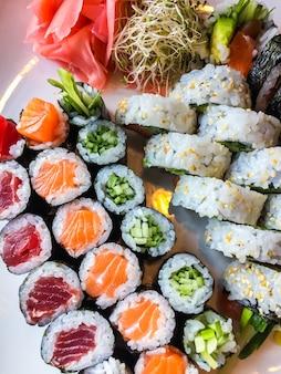 Variedade de rolos de sushi japoneses em um prato branco
