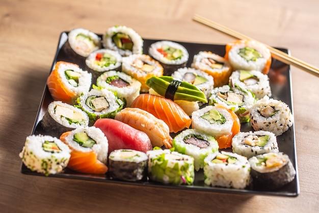 Variedade de rolos de sushi japoneses nigiri sashimi e maki.