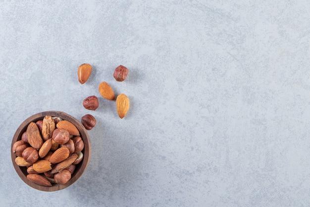 Variedade de saborosas frutas secas e nozes em uma tigela de madeira.