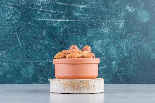 Variedade de saborosas nozes orgânicas em uma tigela com fundo de pedra.