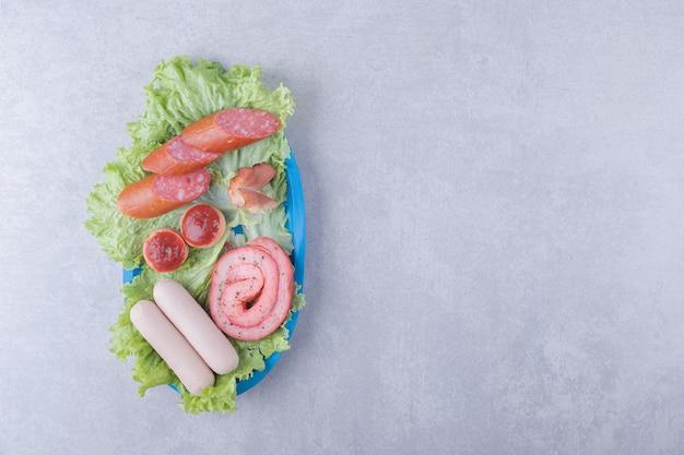 Variedade de saborosas salsichas na placa azul.