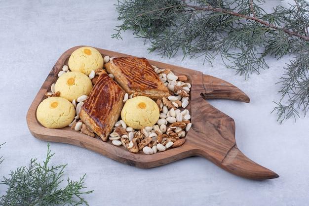 Variedade de saborosos biscoitos na placa de madeira com nozes.