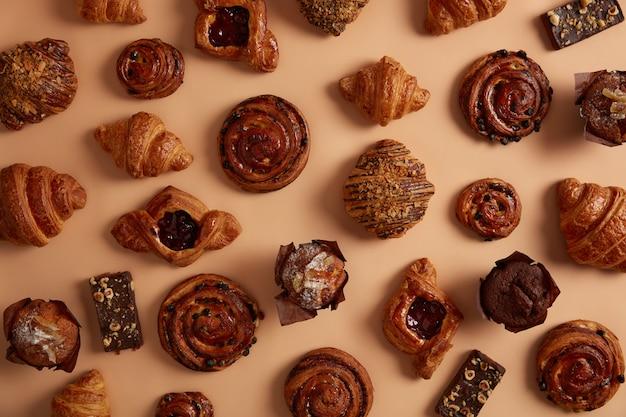 Variedade de saborosos produtos de confeitaria açucarados em vários sabores. pãezinhos, criossants, muffins e barras de chocolate recém-assados. sobremesa doce, lanche gostoso caseiro. produtos de padaria. postura plana