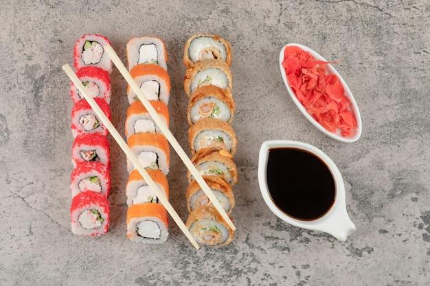 Variedade de saborosos rolos de sushi e molho de soja no fundo de mármore