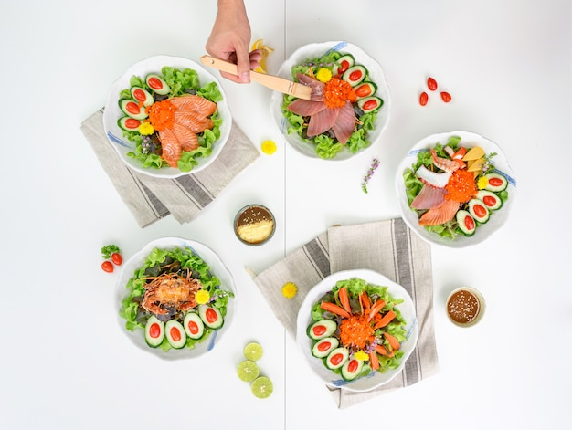 Variedade de salada com salmão, maguro, caranguejo, kani e frutos do mar em cima da mesa