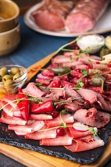 Variedade de salame e lanches na placa de madeira. presunto, salame, salsichas e presunto na tábua de madeira