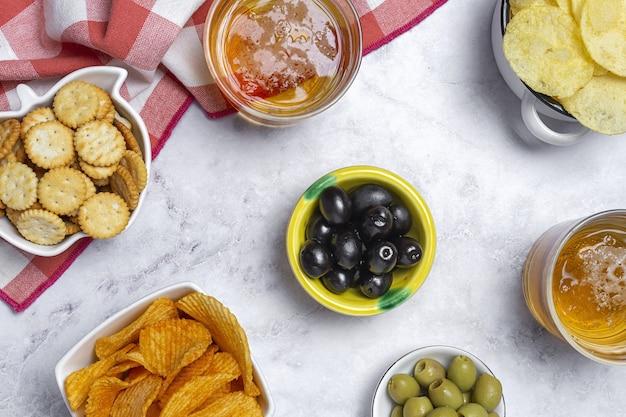 Variedade de salgadinhos em casa com batata frita, cerveja, biscoitos, azeitonas verdes e pretas em mesa de mármore