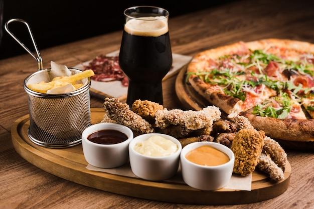Variedade de salgadinhos fritos de cerveja com molhos