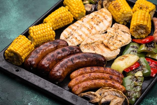 Variedade de salsichas grelhadas, carnes e vegetais. conceito de churrasco de piquenique