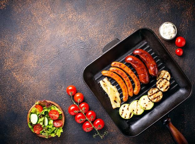 Variedade de salsichas grelhadas e legumes na panela de grelhar