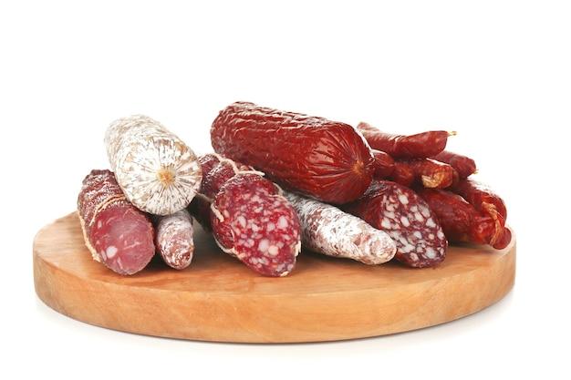 Variedade de salsichas na placa de madeira, isolada no branco