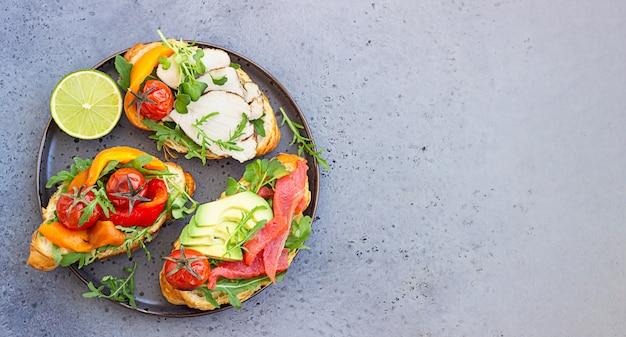 Variedade de sanduíches de croissant com legumes, salmão, peru, abacate e rúcula