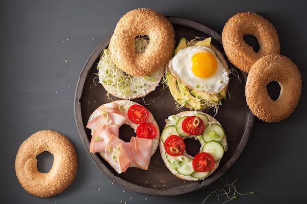 Variedade de sanduíches em bagels: ovo, abacate, presunto, tomate, queijo, brotos de alfafa