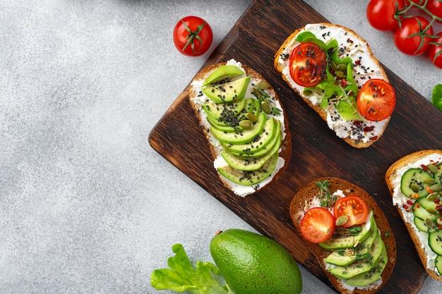 Variedade de sanduíches veganos com abacate e tomate