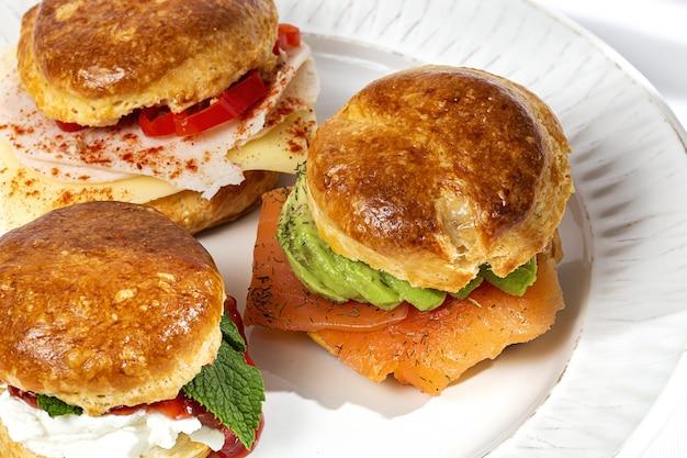 Variedade de scones caseiros com presunto, queijo, abacate, salmão, queijo creme e geléia de morango