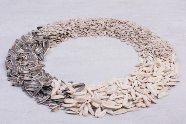 Variedade de sementes de girassol na superfície branca.