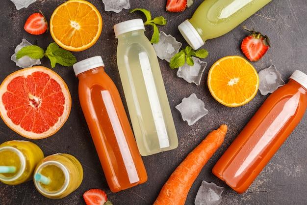 Variedade de smoothies coloridos ou garrafas de sucos de frutas, frutas e vegetais, vista de cima, mesa escura. programa de desintoxicação, conceito de estilo de vida saudável.