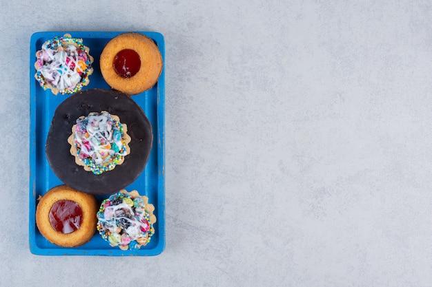 Variedade de sobremesa pequena em uma bandeja azul na mesa de mármore.