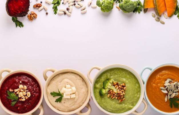Variedade de sopa de creme de vegetais coloridos com brócolis, beterraba, feijão branco e abóboras