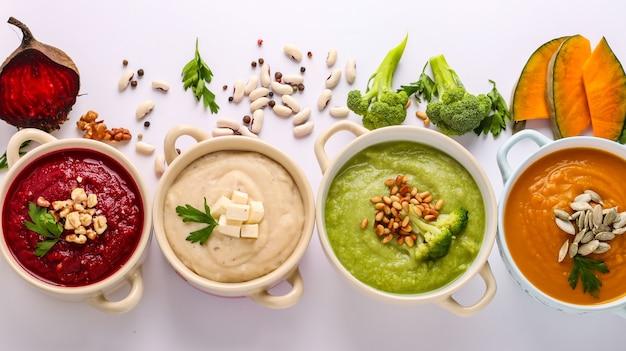 Variedade de sopas de creme de vegetais: com brócolis, feijão branco, beterraba e abóboras, ingredientes para sopa, conceito de alimentação saudável, vista superior, orientação horizontal