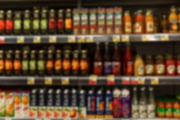 Variedade de sucos embalados nas prateleiras da loja. vista frontal. borrado.