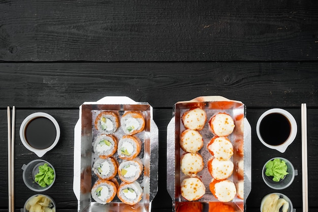 Variedade de sushi e rolos diferentes de, salmão e atum em conjunto de conceito de entrega de comida, na mesa de madeira preta