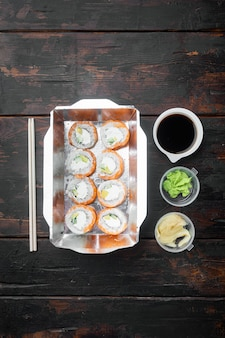 Variedade de sushi e rolos diferentes de, salmão e atum em conjunto de conceito de entrega de comida, na velha mesa de madeira escura