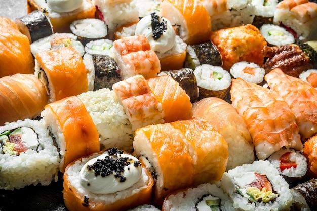 Variedade de sushi, maki e pãezinhos. na mesa rústica