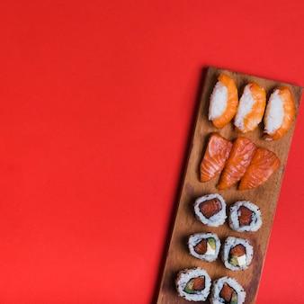 Variedade de sushi na bandeja de madeira contra o pano de fundo vermelho com espaço de cópia para escrever o texto