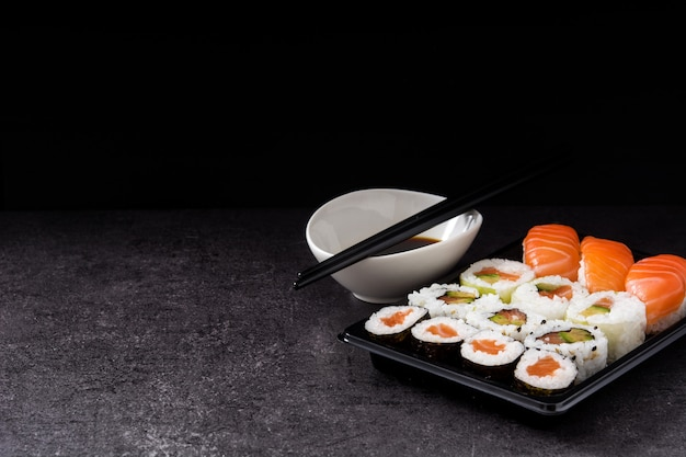 Variedade de sushi na bandeja preta e molho de soja