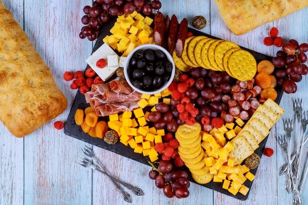 Variedade de tábua de charcutaria, queijo, azeitonas, frutas e presunto na mesa de madeira