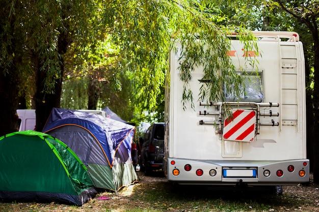 Variedade de tendas e van para acampar