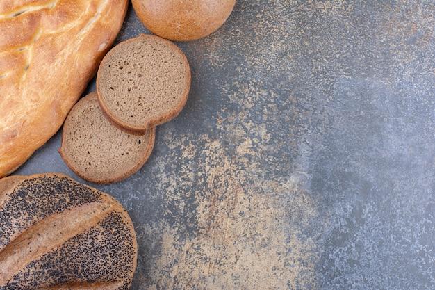 Variedade de tipos de pães agrupados na superfície de mármore