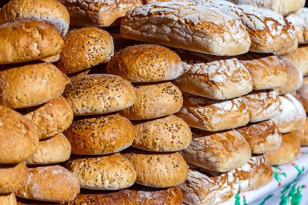 Variedade de tipos diferentes de pão caseiro fresco para a venda no close-up do mercado.