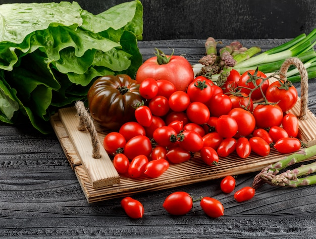 Variedade de tomate em uma bandeja de madeira com alface, aspargos, cebolinha, vista de alto ângulo na parede de madeira e escura