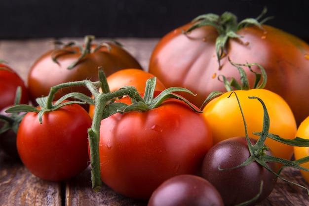 Variedade de tomates coloridos orgânicos frescos na superfície de madeira.