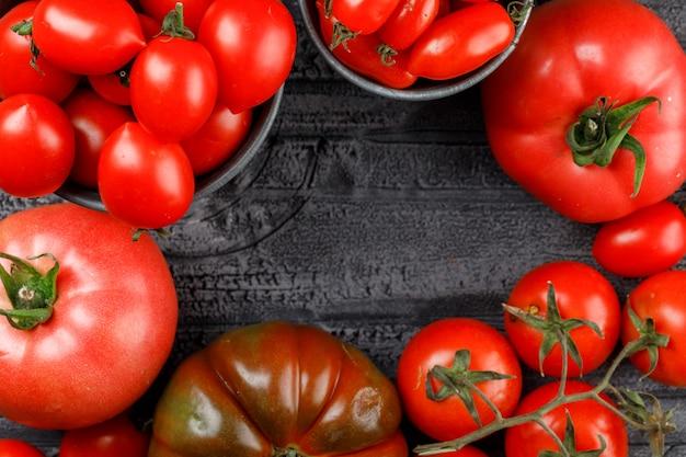 Variedade de tomates em mini baldes na parede de madeira cinza, close-up.