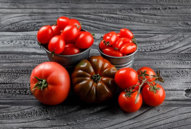 Variedade de tomates em mini baldes na parede de madeira cinza, vista de alto ângulo.