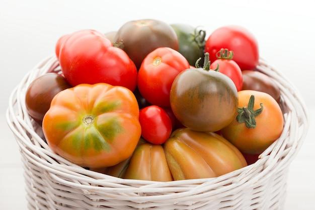Variedade de tomates frescos na cesta em madeira