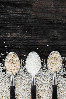 Variedade de três diferentes tipos de arroz no pano de fundo texturizado de madeira
