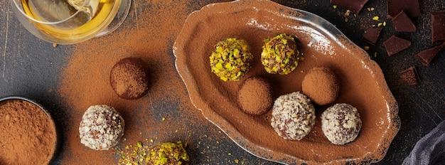 Variedade de trufas de chocolate amargo caseiras com cacau em pó, pistache, amêndoas em textura de fundo marrom escuro. vista superior, copie o espaço.