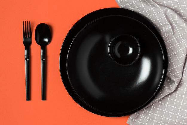 Variedade de utensílios de mesa em fundo laranja e pano