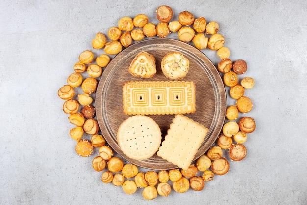 Variedade de vários biscoitos empilhados na placa de madeira e rodeados por chips de biscoito no fundo de mármore. foto de alta qualidade